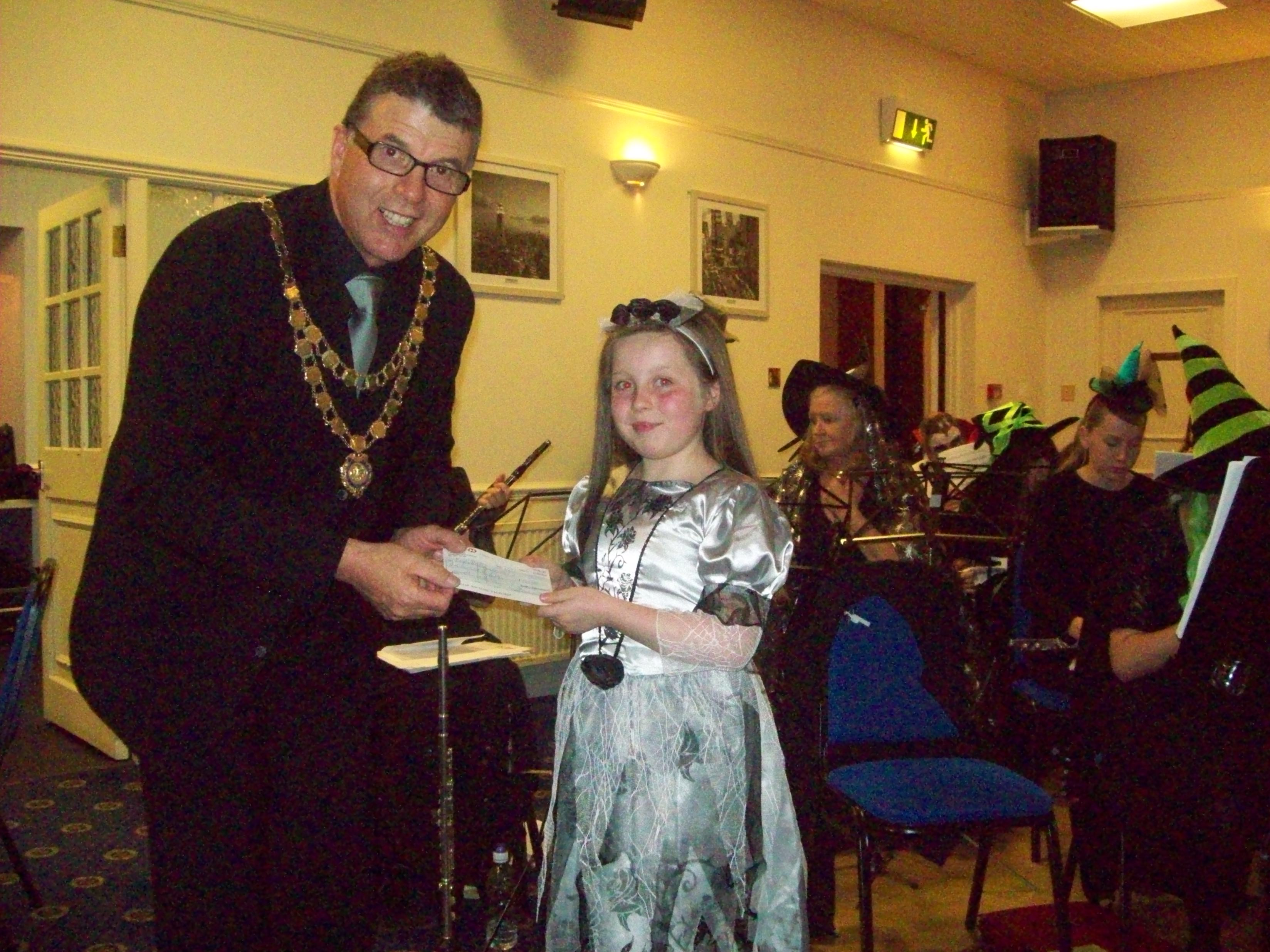 Mayor of Maghull Cllr Steve Kermode is presented with the cheque from the money raised at the Maghull Wind Orchestra Halloween Concert by Faye Kay.