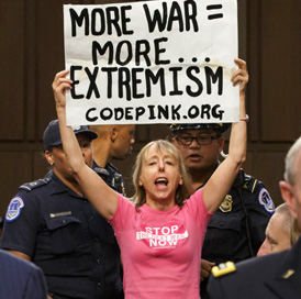 "Medea holding ""More War = More Extremism"" sign"
