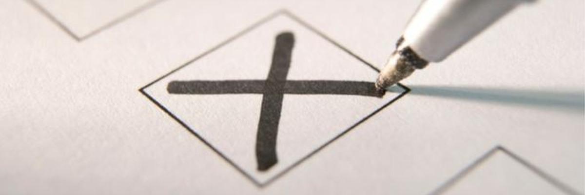 A pen marking an X in a box.