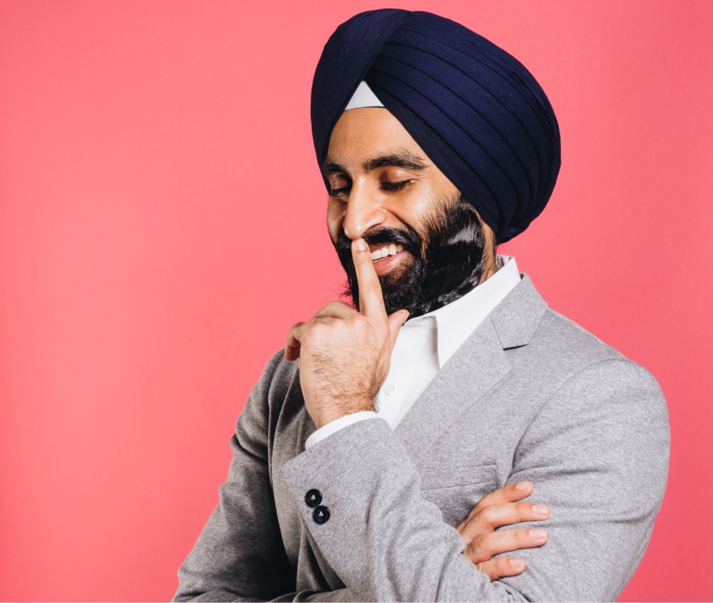 Photo of Gurwin Singh Ahuja, a leader who uses NationBuilder, wearing a grey suit and photographer on a pink background. He is looking down, smiling, and holding a finger to his mouth.