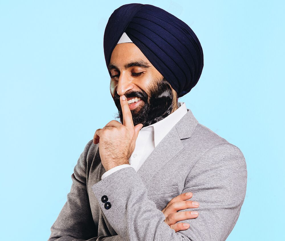 Photo of Gurwin Singh Ahuja, a leader who uses NationBuilder, wearing a grey suit and photographed on a blue background. He is looking down, smiling, and holding a finger to his mouth.