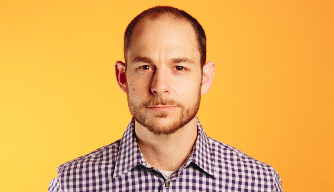 Portrait of Brian Rosenbaum, a leader who uses NationBuilder, against a yellow background, wearing a purple and white checked shirt.