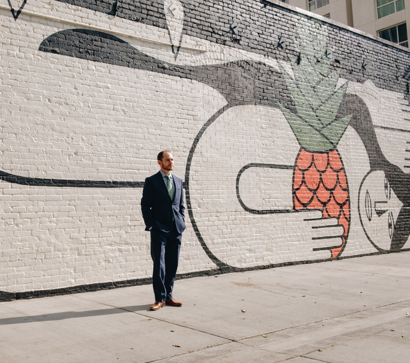 Portrait of Brian Rosenbaum, wearing a suit, standing in front of an enormous and beautiful black and white and pink mural in Downtown Los Angeles.