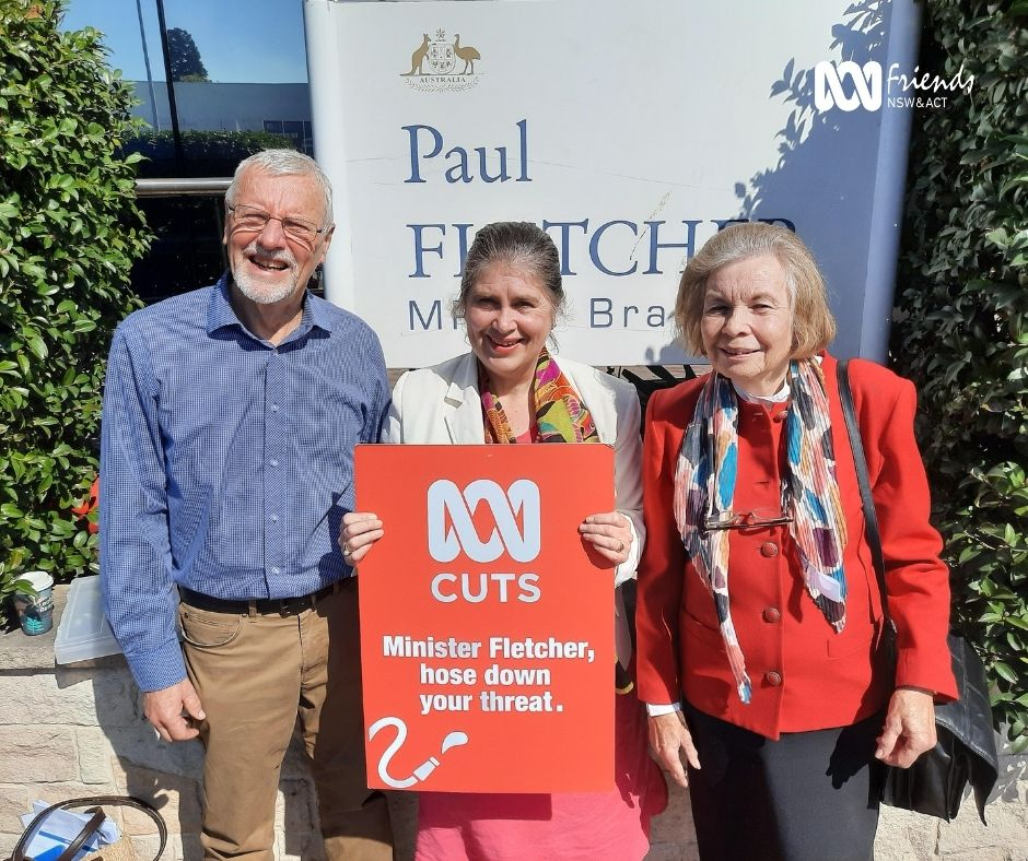 Lindsay Somerville, Janine Kitson, and Kate Reid from ABC Friends outside Minister for Communications Paul Fletcher's office on Sydney: Holding an orange sign reading: ABC Cuts: Minister Fletcher, hose down your threat.