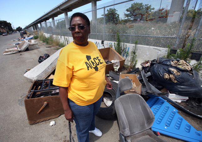 ACCE member stands in front of illegally dumped trash in East Oakland. Demands that the city clean up neglected parts of Oakland.