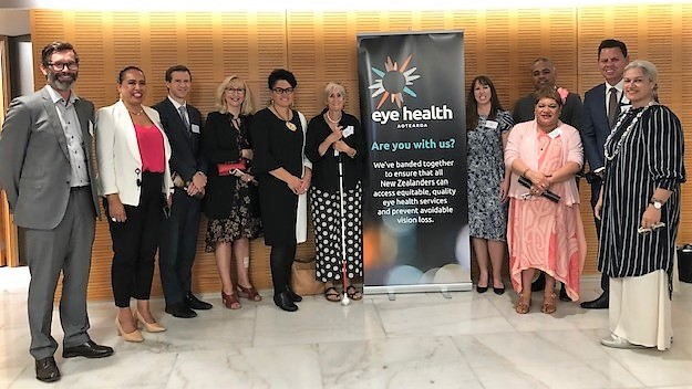 Eye Health Aotearoa trustees, supporters and MPs pose next to EHA banner at parliament