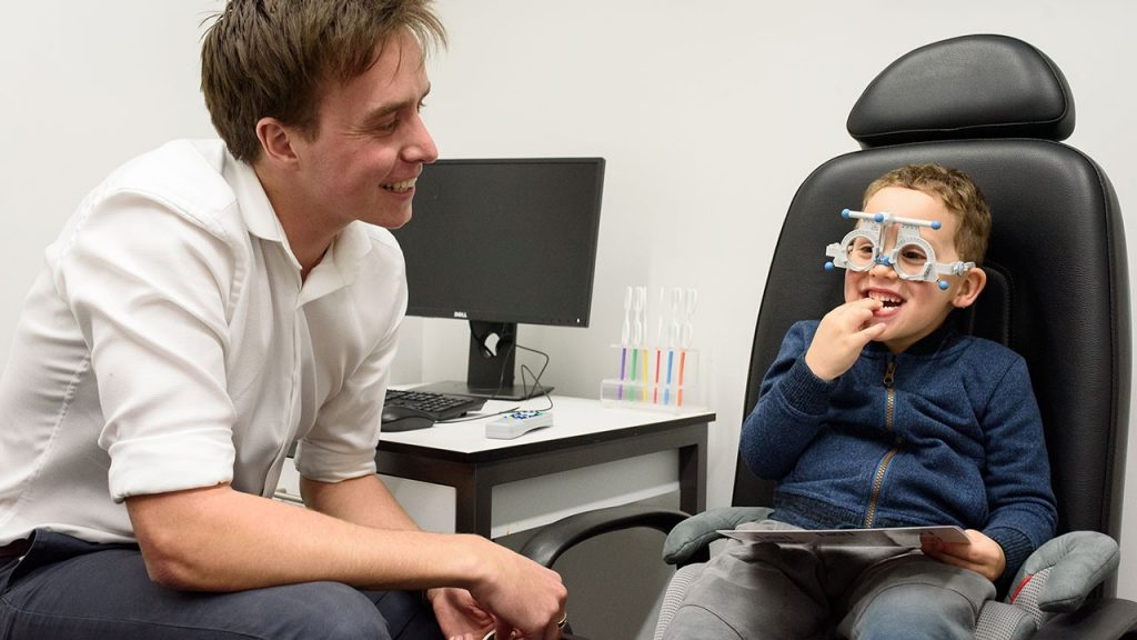 Optometry student Robert Burnie performs a vision test on a child