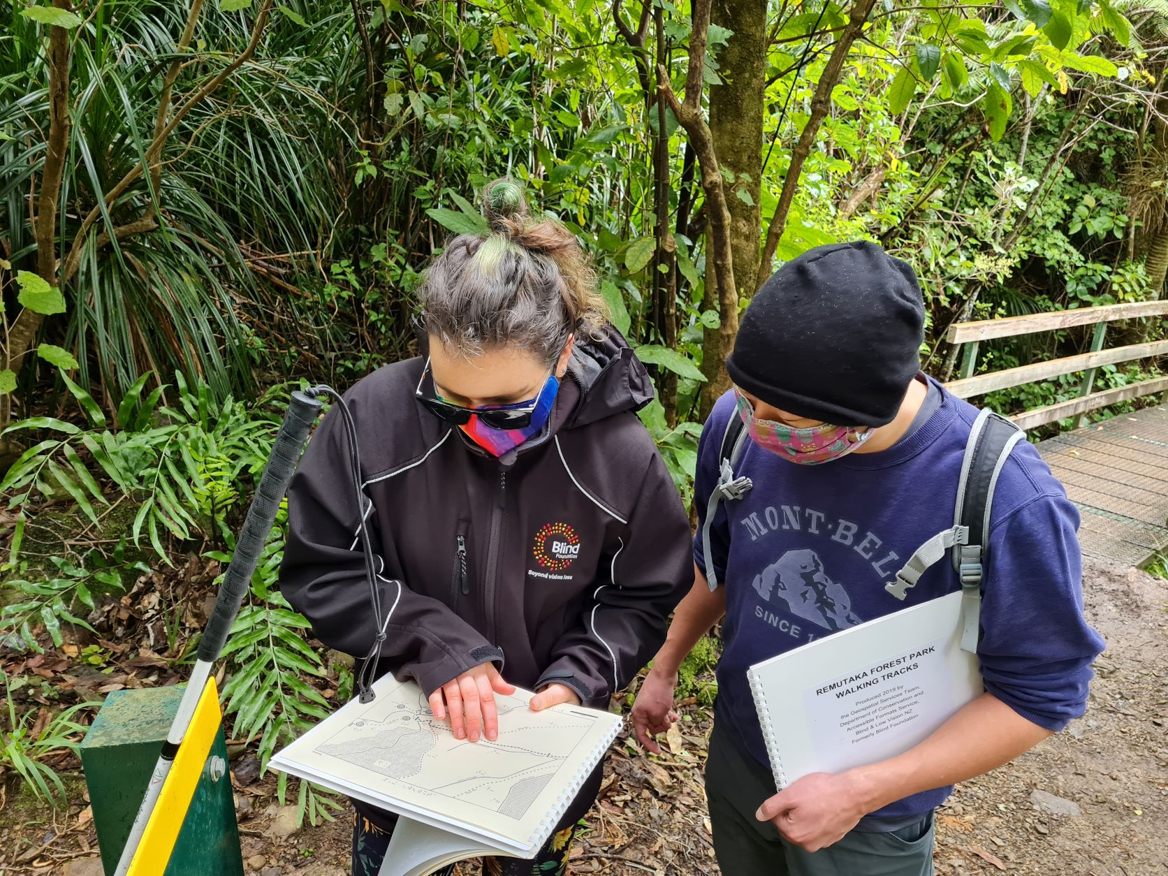 Mary and friend reading braille map of Remutaka Forest Park, near a bridge and a DOC sign, surrounded by trees.  Mary is wearing a black Blind Foundation jacket, both wearing colourful face masks.