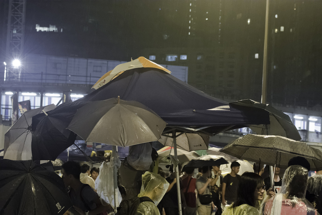 Pro-Democracy supporters standing in the rain in Hong Kong on October 1 (photo by Lamuel Chung)