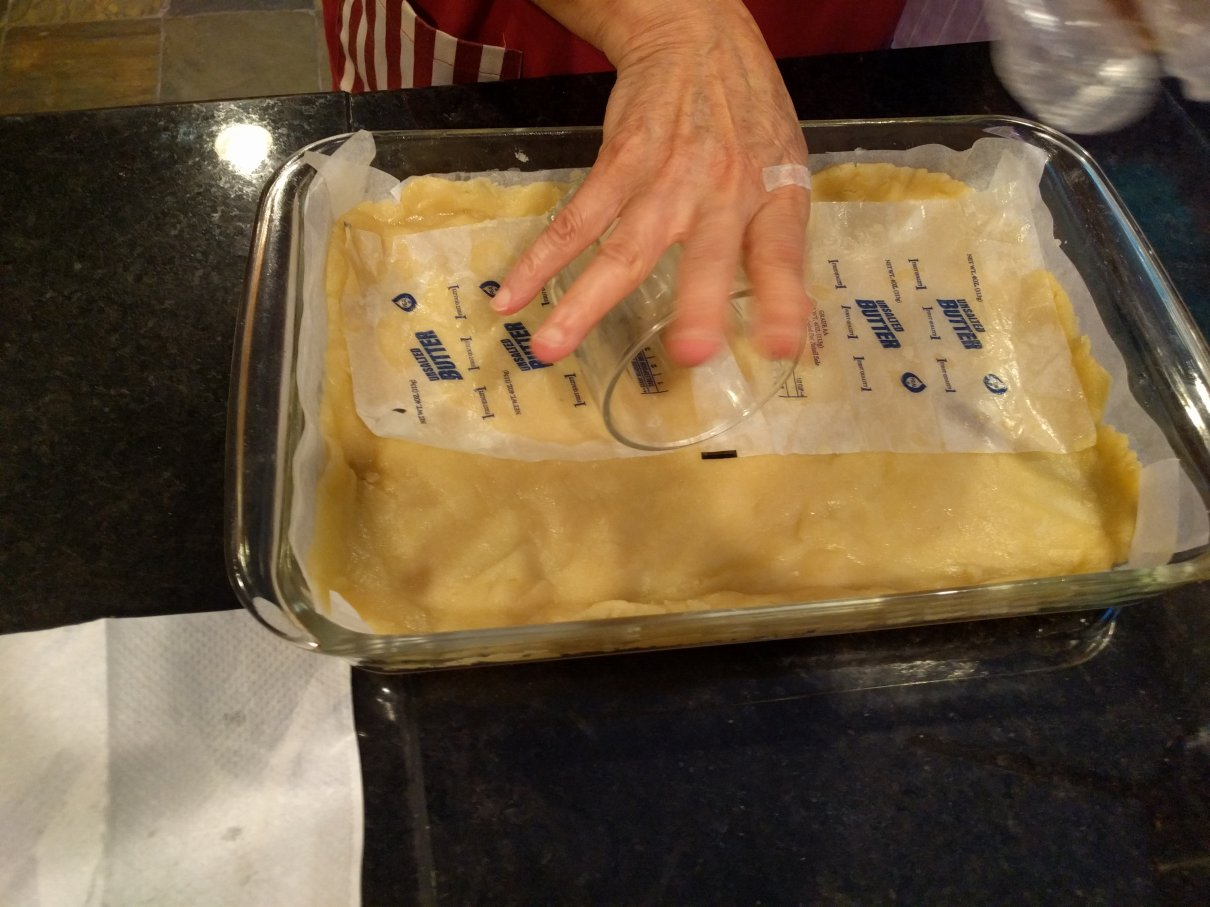 Press the dough into the pan. A smooth glass can help roll it out.