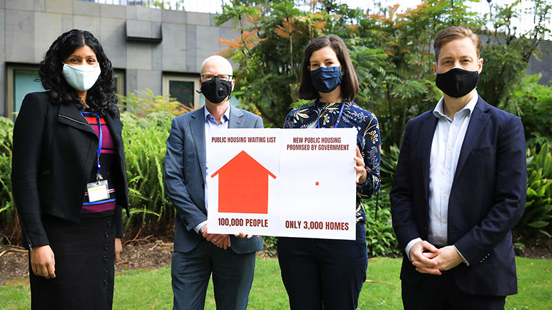 Greens MPs holding a sign showing that there are only 3,000 new homes being built for 100,000 people on the public housing waiting list