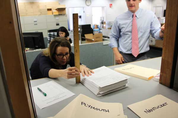 A volunteers measures the stack of delivered certified signatures.