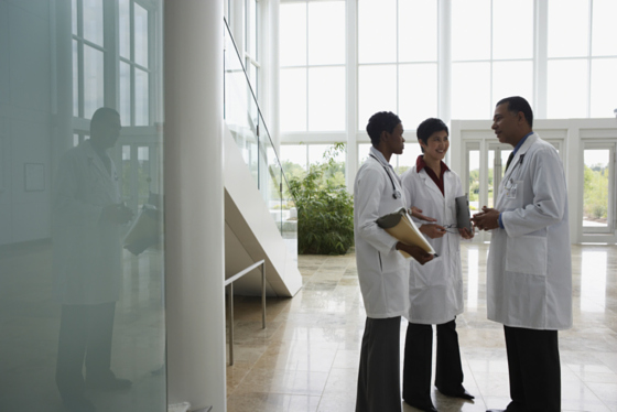 picture of 3 doctors talking in atrium in white lab coats