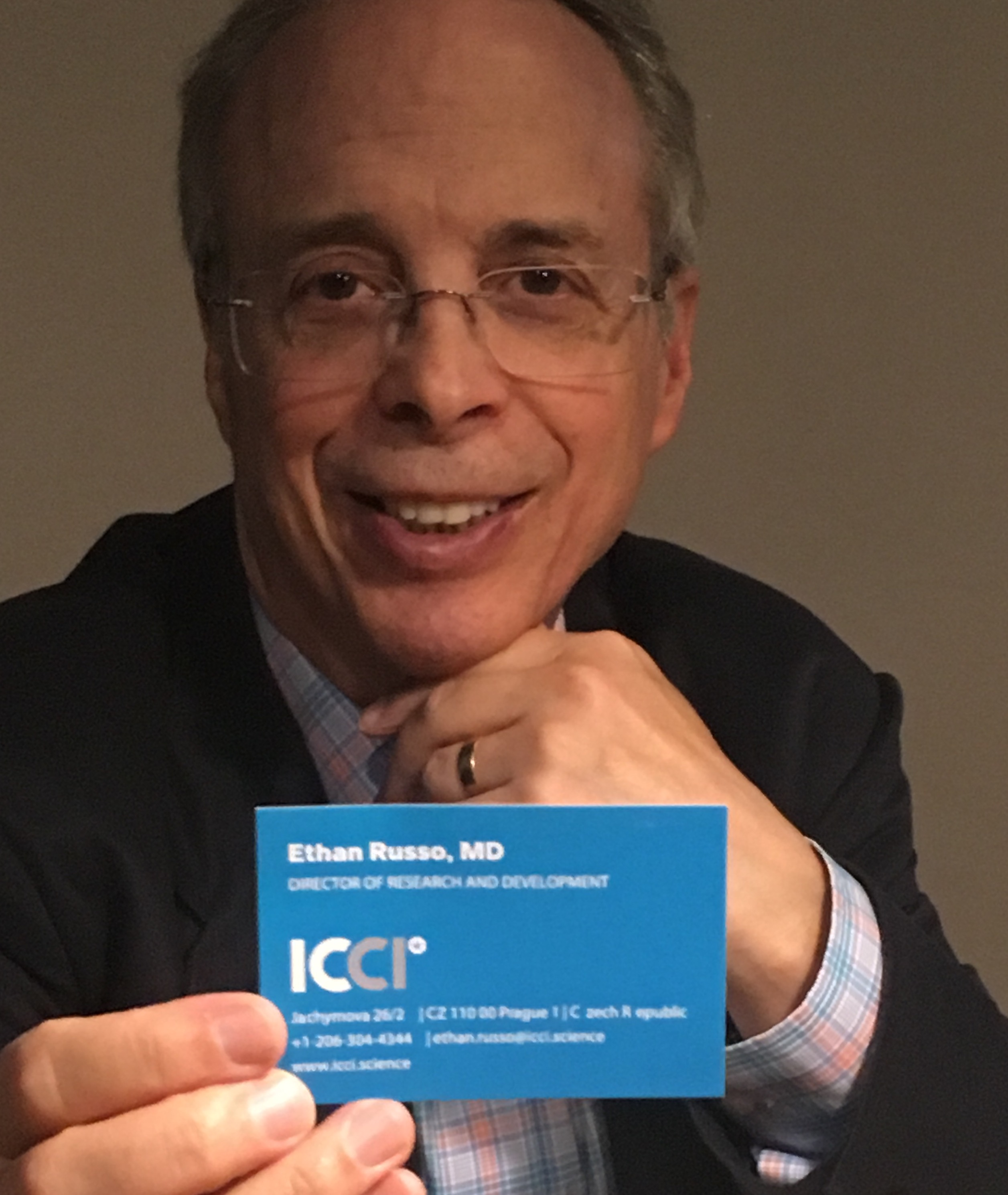 Photograph of Dr. Ethan Russo holding in a foreground a business card with the ICCI logo and his name on it.