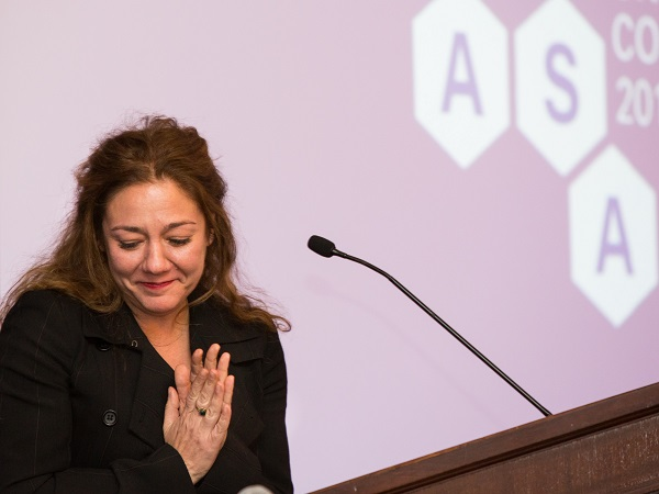 Steph Sherer standing at a podium in front of an ASA Backdrop