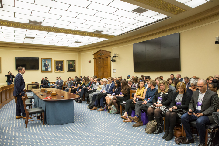 A large group of people dressed formaly in a hearing room in the U.S. Capitol Building. Most are seated but one man is standing behind a tale speaking to the group. A photographer stands in the corner. The room is bright with beige walls and blue carpeting. The walls feature television screens and portraits of lawmakers.