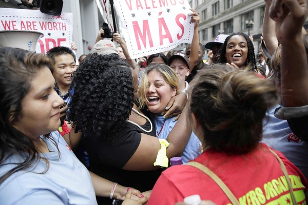Walgreens employee Trinece Mosley, 24, left, congratulates fellow employee Teresa Anaya, 23, center, with a hug after she walked off the job in solidarity with Chicago fast-food workers, retail workers and supporters as they rally outside Walgreens, 151 N. State St., Thursday, Aug. 1, 2013 as part of a week of strikes in seven cities across the country including New York City, St. Louis, Detroit, Milwaukee, Kansas City and Flint, as workers fight for $15/hour and the right to form a union