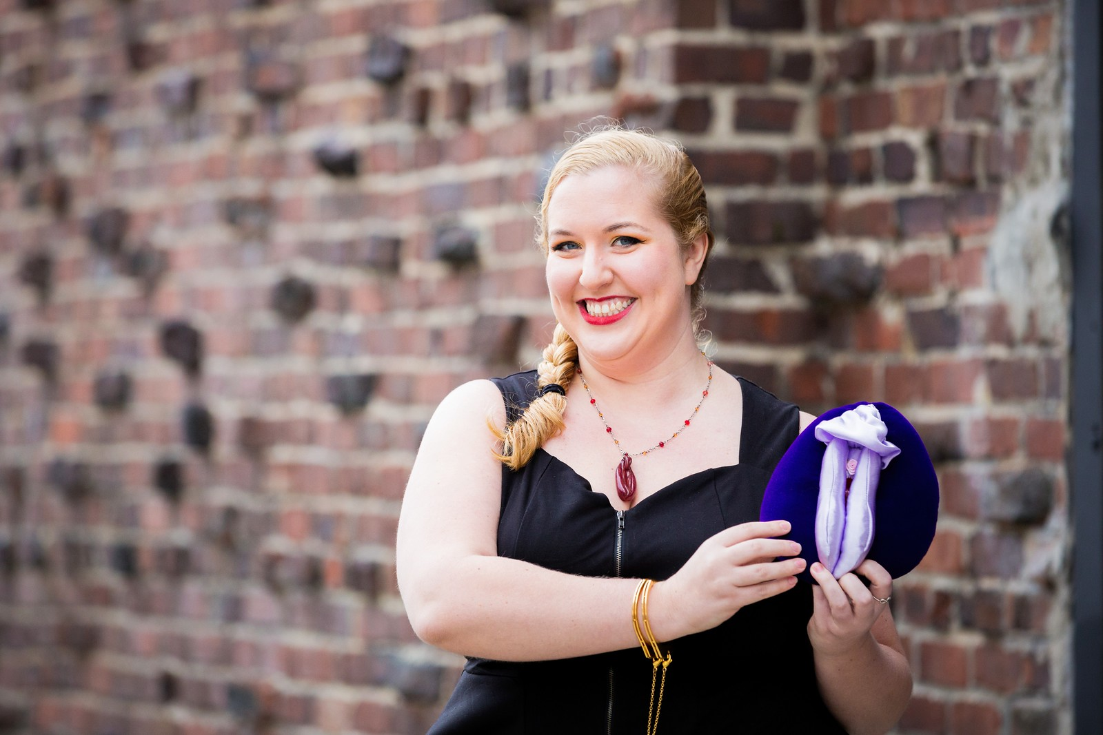 Image of a feminine person with blonde hair in a side braid, red lipstick, gold handcuff bracelets, and a black top, standing in front of a brick wall holding a purple plush vulva puppet.