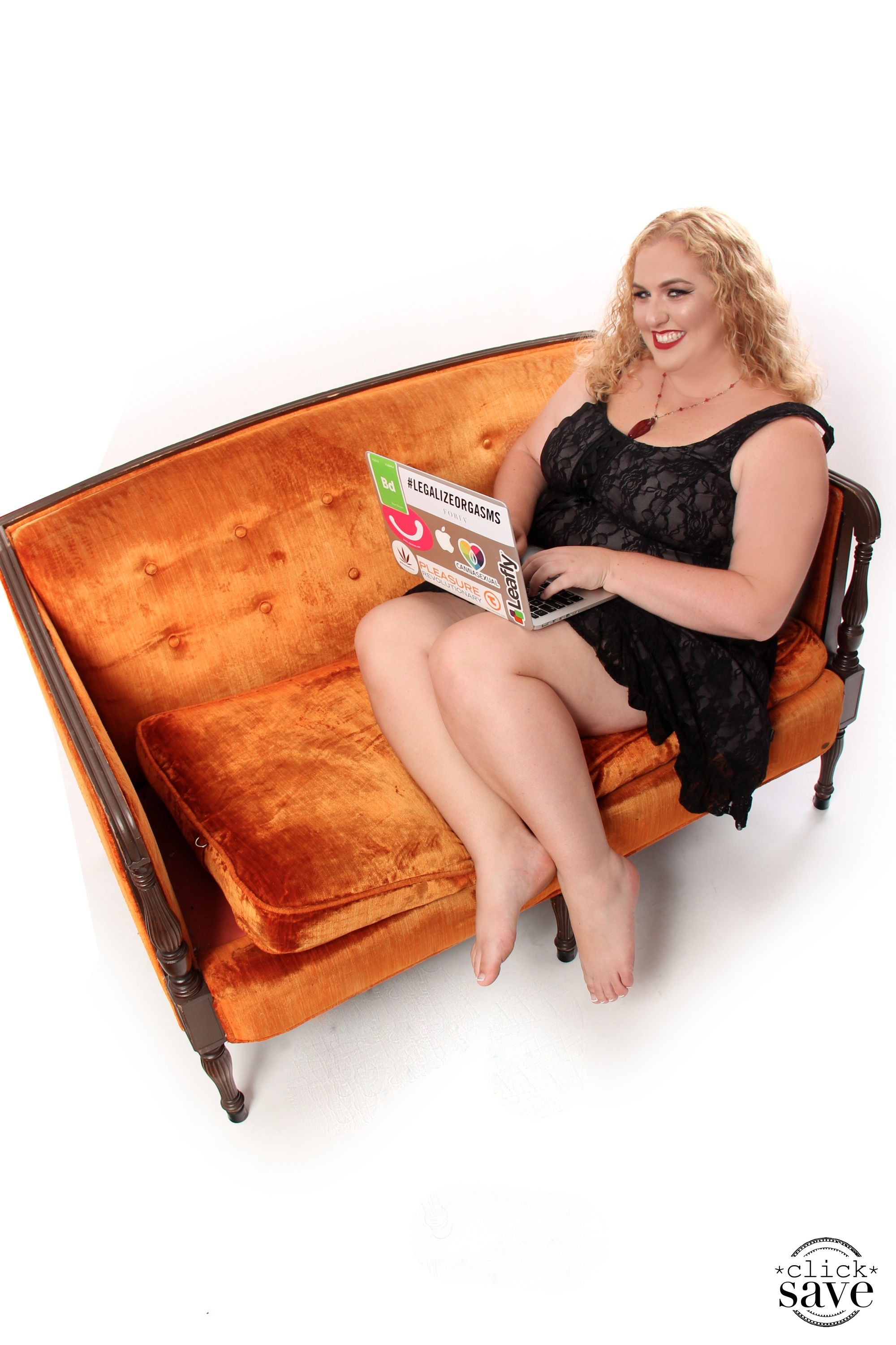 Image of Ashley on orange couch with laptop