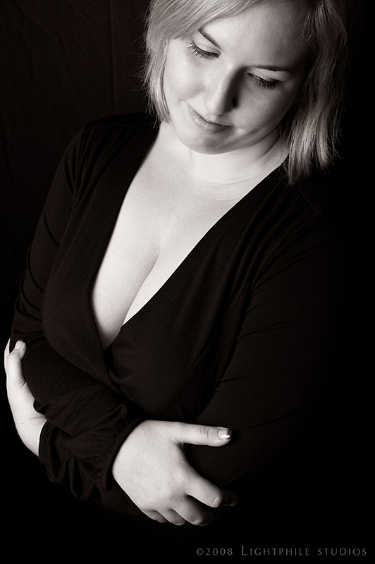 black and white portrait of  a cis woman's torso in a black shirt
