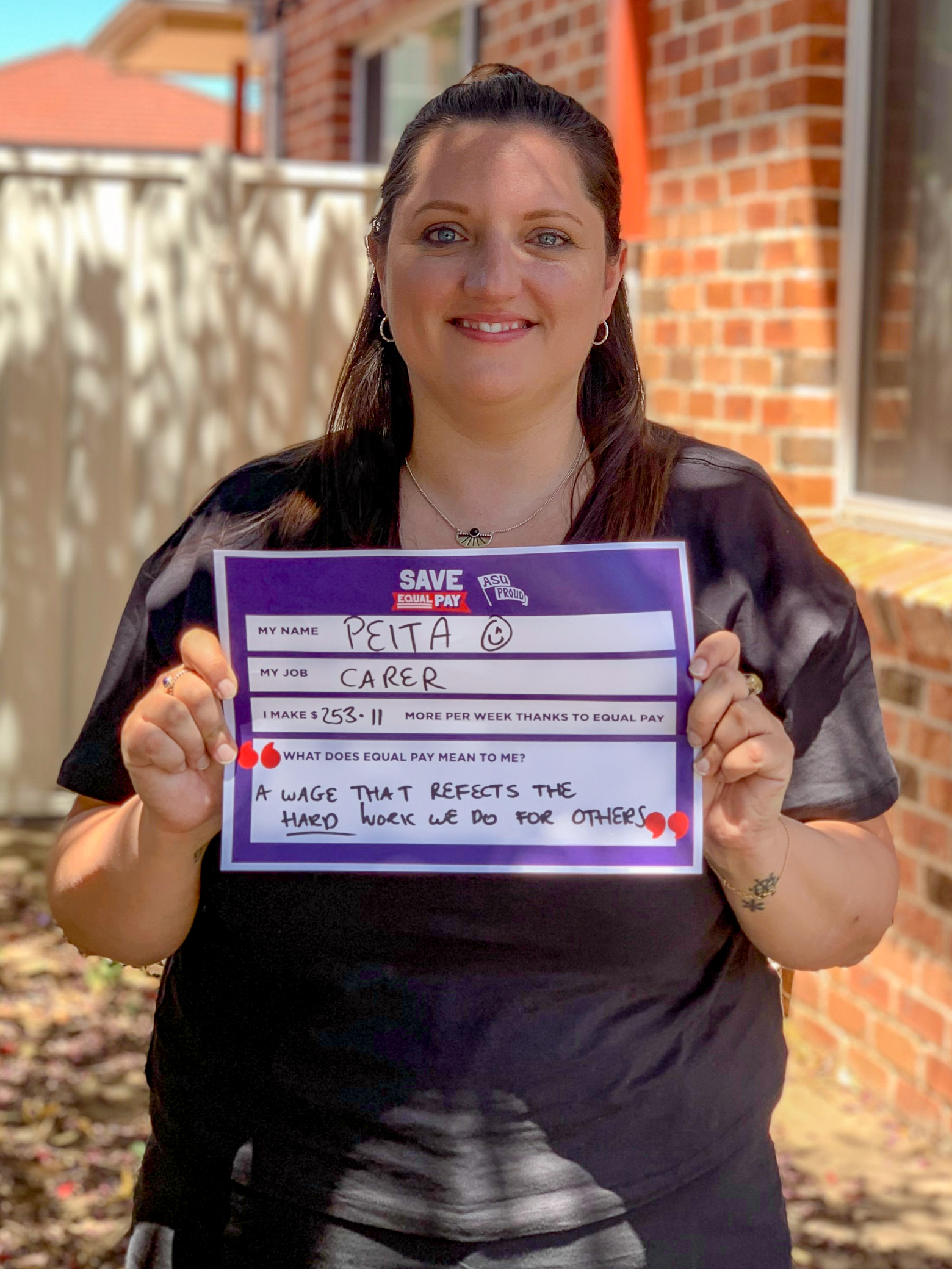 Peita holding a sign about what Equal Pay means to her