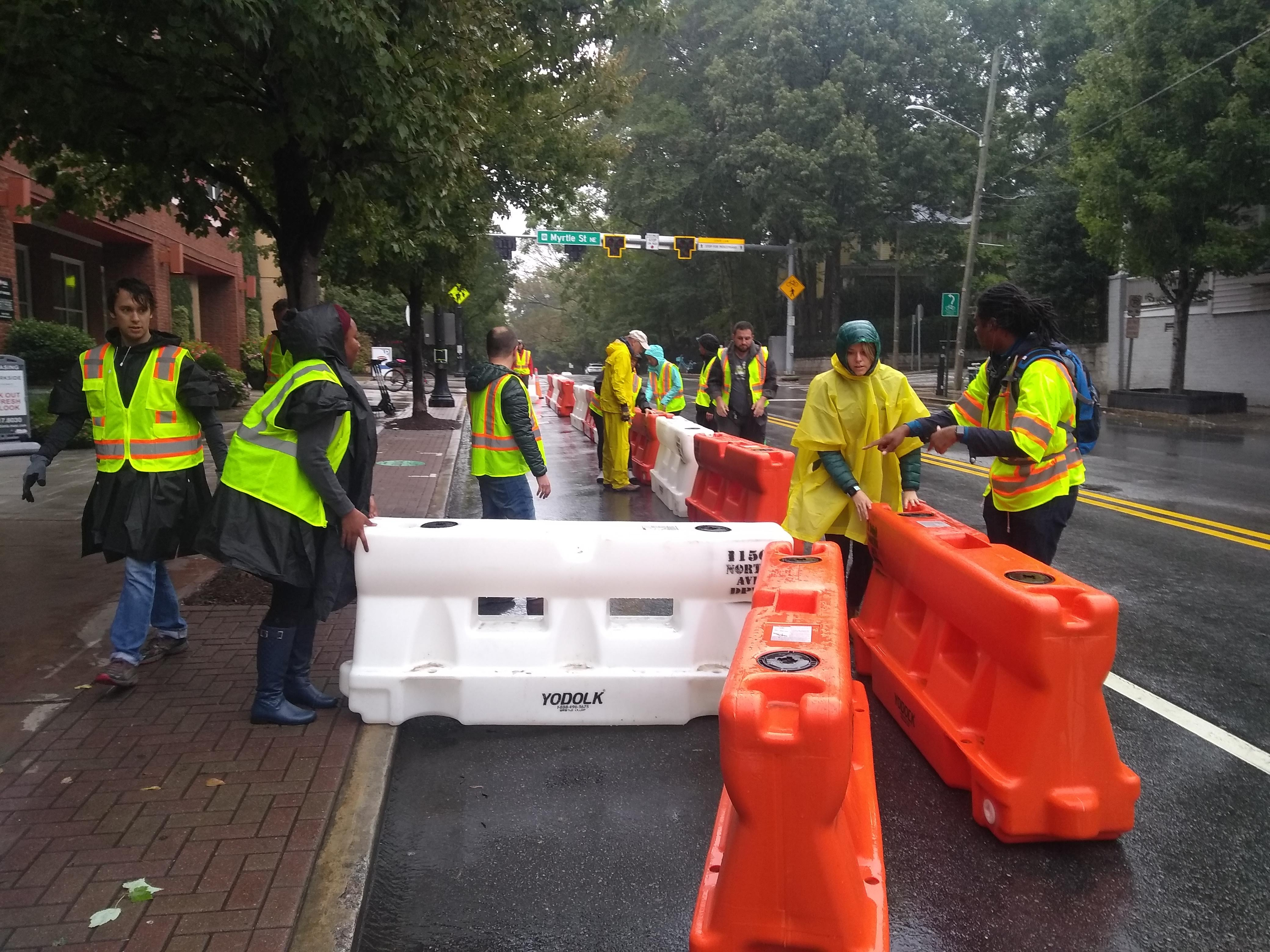 Volunteers move plastic barricades to create a protected bike lane on 10th Street in Midtown Atlanta