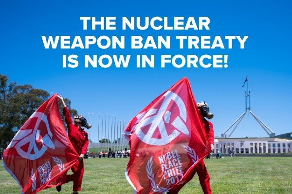 ICAN volunteers clad in gas masks run with red ICAN flags in front of Parliament house to celebrate the nuclear weapon ban treaty coming into force
