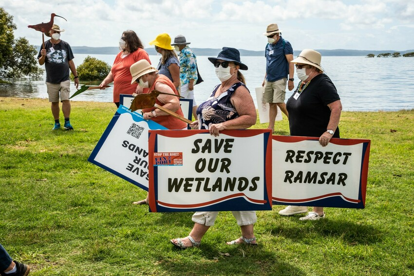 Protesters hold signs to demonstrate against Walker Corporation's Toondah Harbour development
