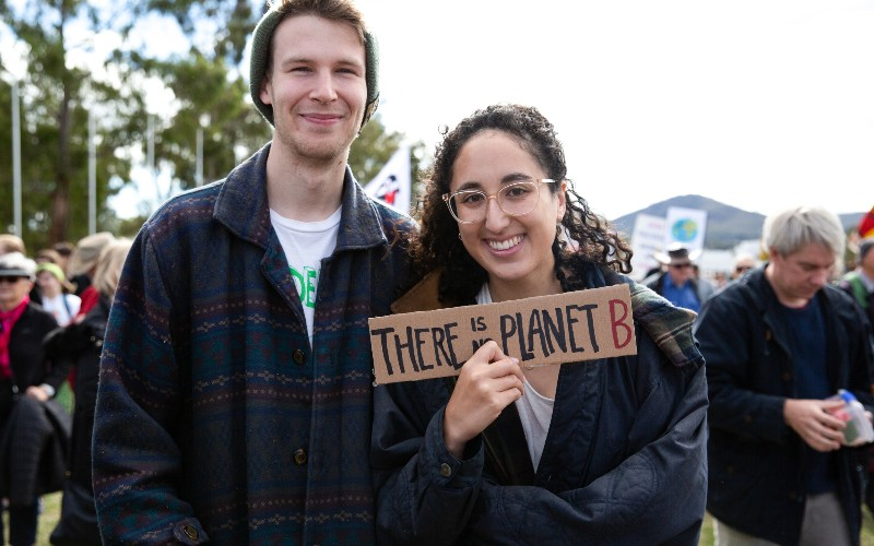Two people smile at the Stop Adani Convoy. One holds up a sign that says: \