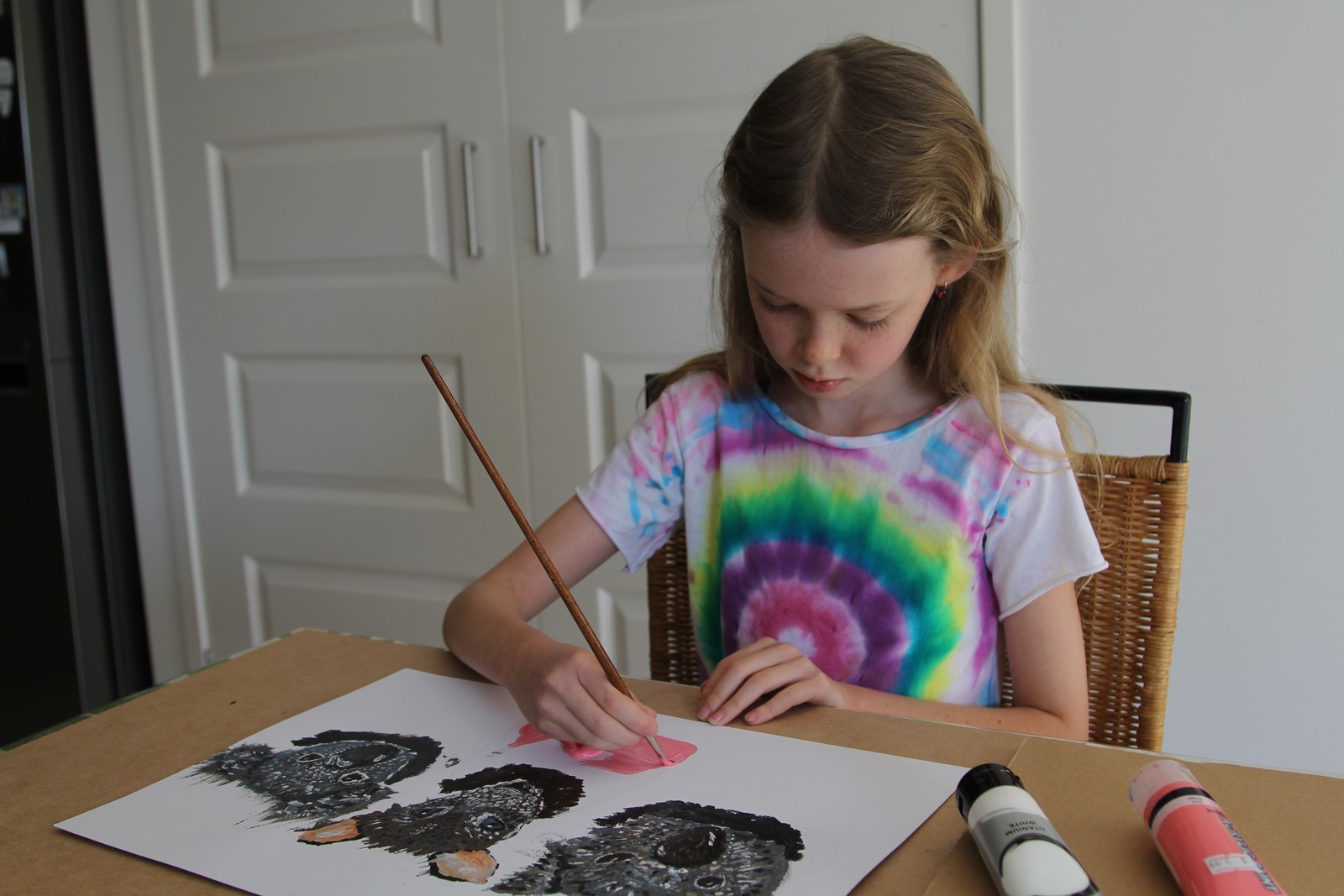 Girl with blonde hair painting native Australian animals