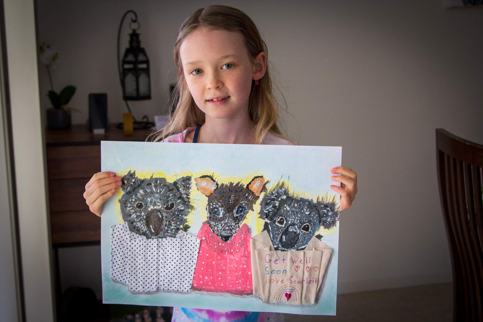 Young girl holds a painting of three Australian animals