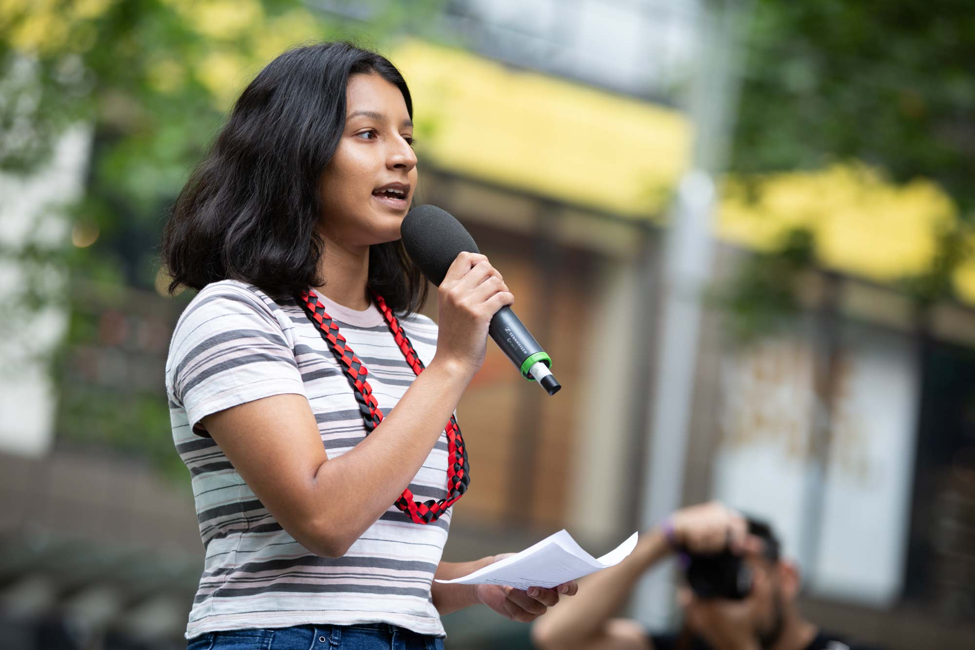 A young woman holding a microphone speaks at a rally