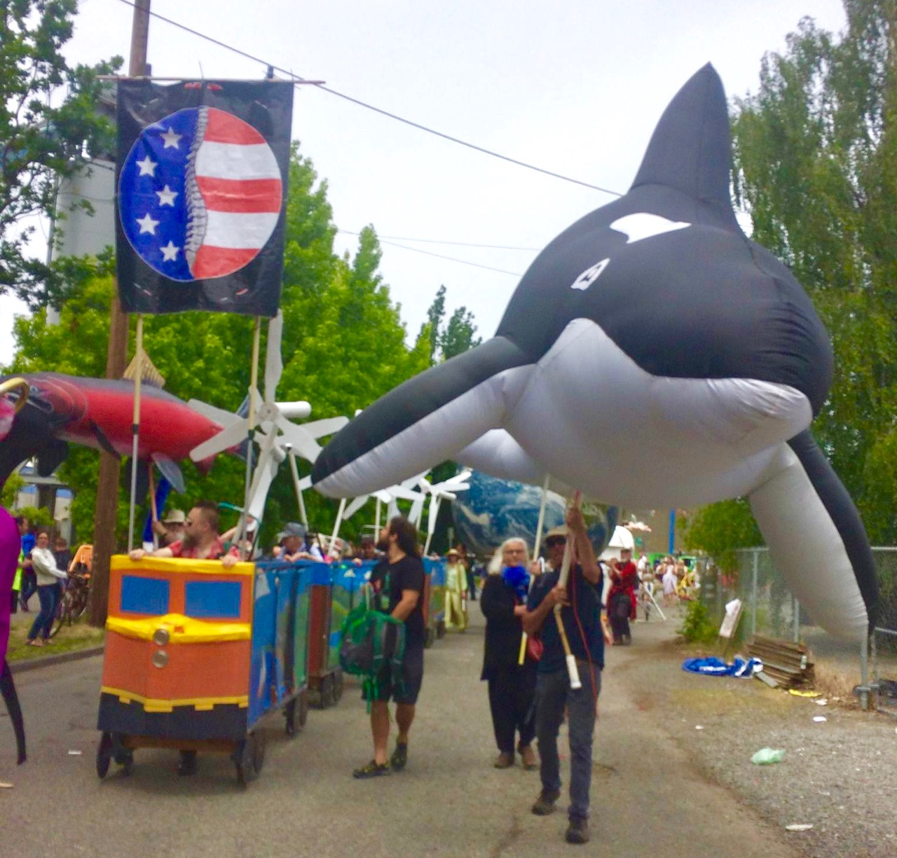 Orca_and_Backbone_flag_with_ecotopia_train_in_solstice_parade_2017.jpg