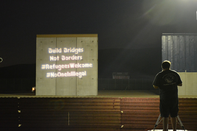 Small_Build_Bridges_Not_Borders_on_border_wall_projector_with_San_Diego_Solidarity_Brigade_Guerrilla_Light_Projection_(photos_by_Jill_Marie_Holslin_and_OLBSD).jpg