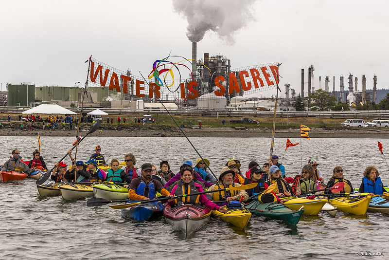 Small_800px_Water_is_Sacred_during_Indigenous_Day_Flotilla_at_Break_Free_PNW_2016_Photo_taken_by_John_Duffy_27104327905_dac087b675_c.jpg
