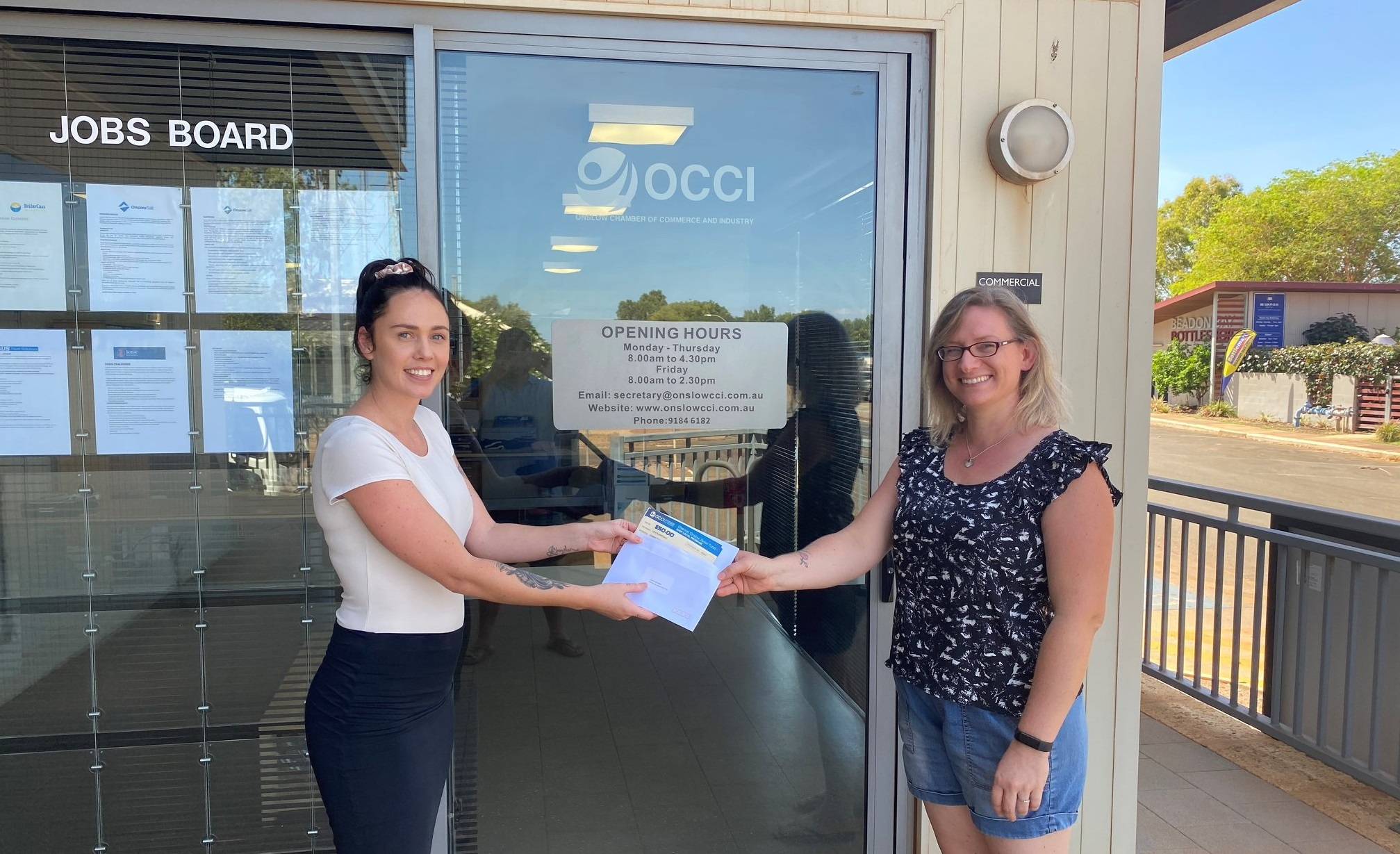 Shelley Alaniz from the Onslow Chamber of Commerce and Industry presents resident Lena Kustermann with a Shop Local voucher as part of the relief fund