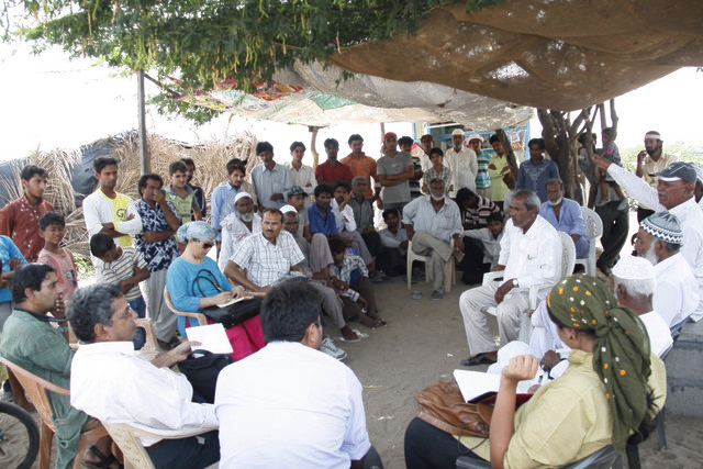 Fisherfolk and members of the fact-finding committee discuss the impacts of the developments of Tata and Adani. (Soumya Dutta at far left, in green)
