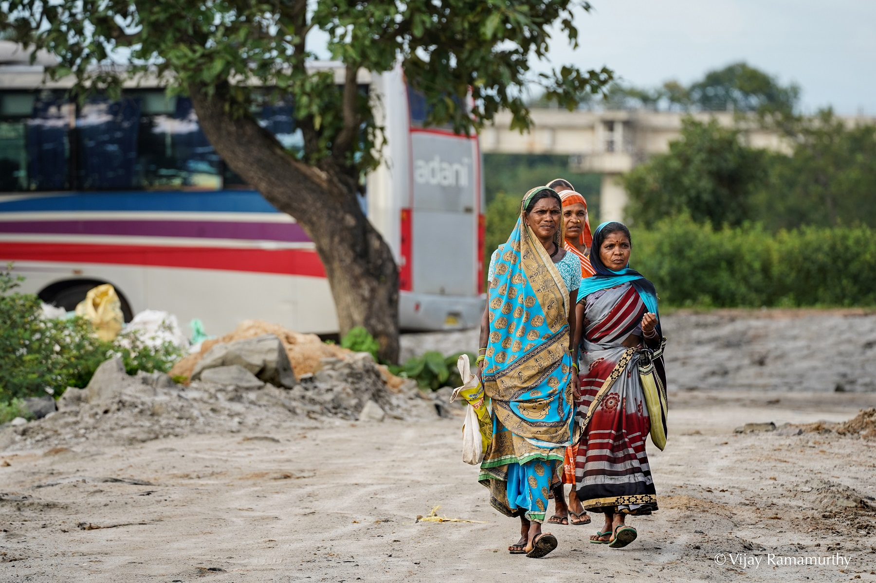 Adivasi women walk along what used to be a forest path, with an Adani coal workers bus in the background. Photo V. Ramamurthy