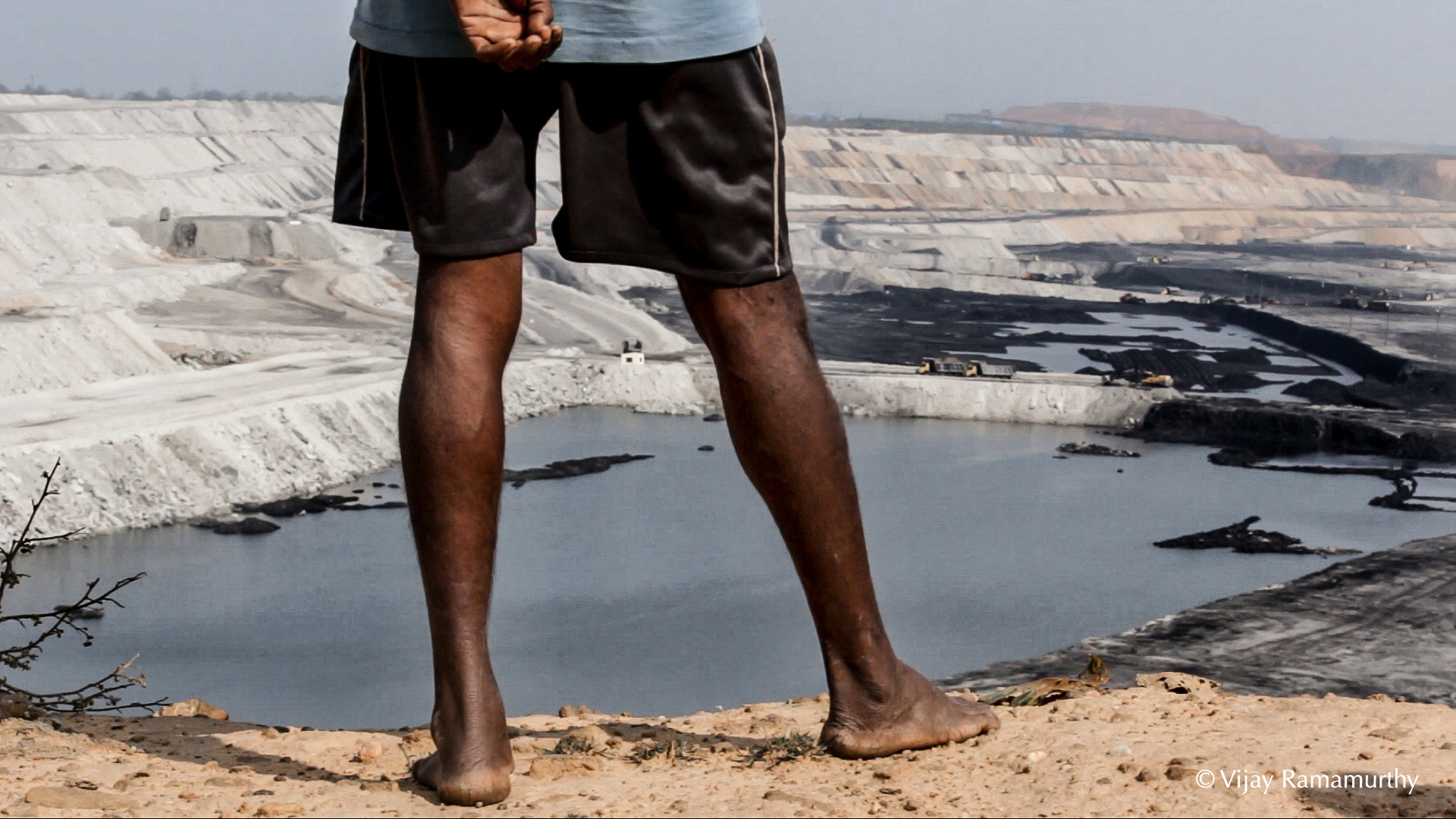An indigenous forest dweller of India's Hasdeo area overlooks the Adani-operated PEKB mine that obliterated forests and ancestral lands. Photo V. Ramamurthy