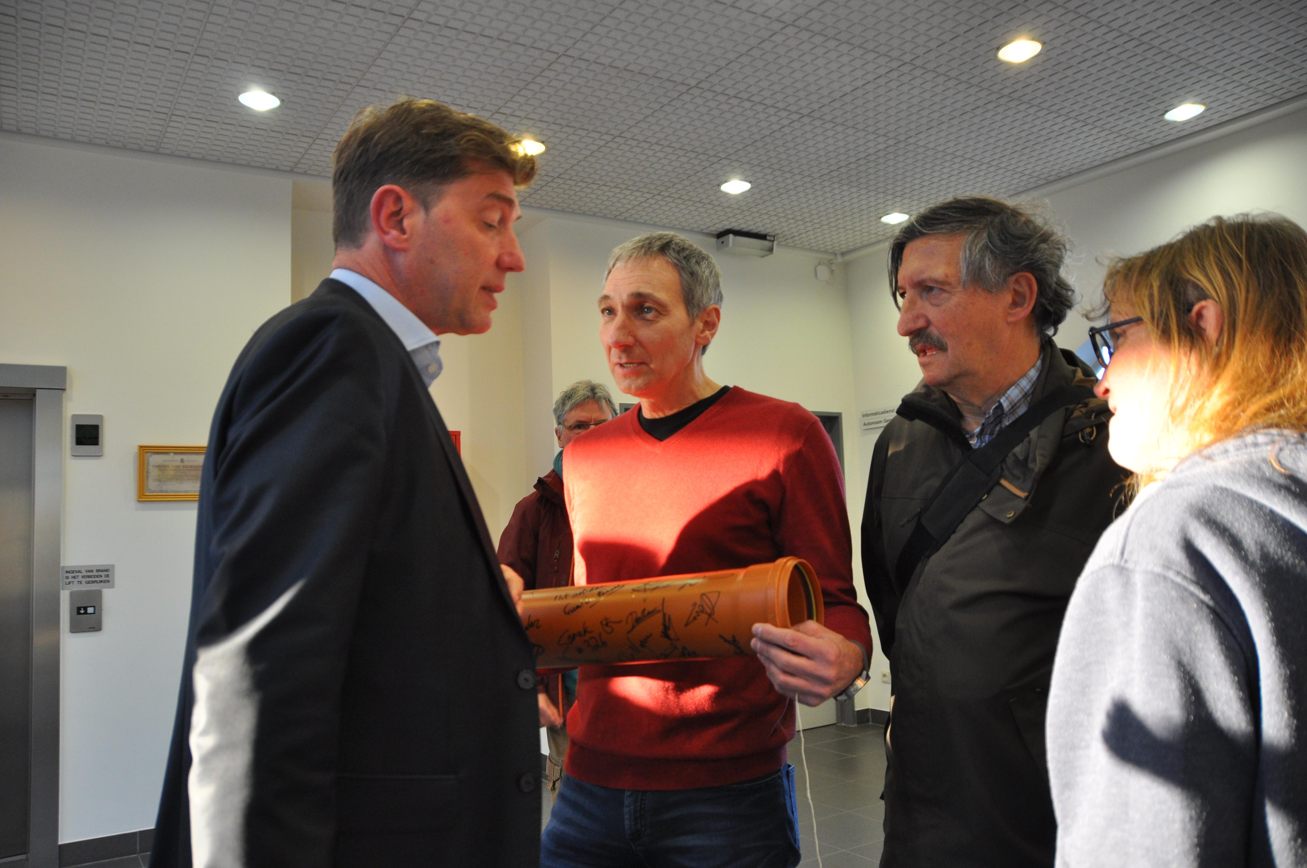 Rudy Van Rompaey overhandigt de buis aan de N-VA burgemeester