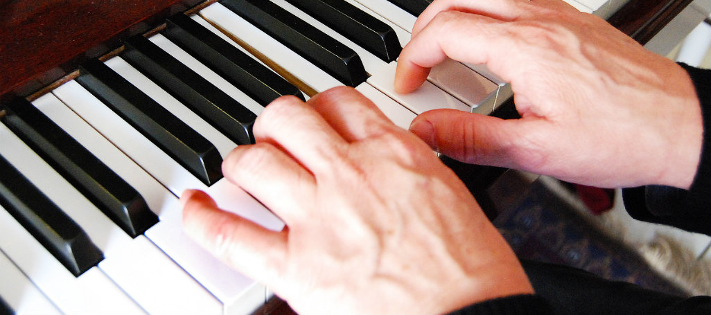 two_adult_hands_on_Yamaha_piano_1026x455.jpg