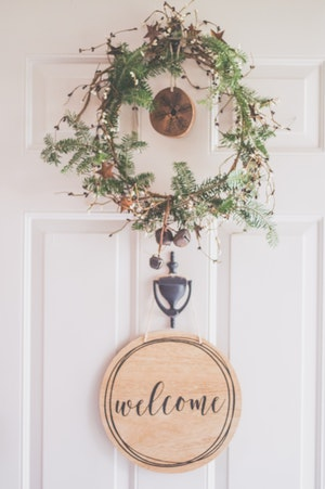 photo-of-a-white-door-with-a-hanging-wreath-and-welcome-1652394.jpg