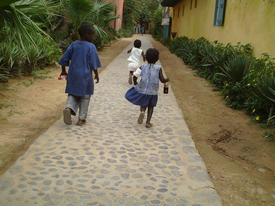 children walking and running down a street filled with colorful houses and green plants