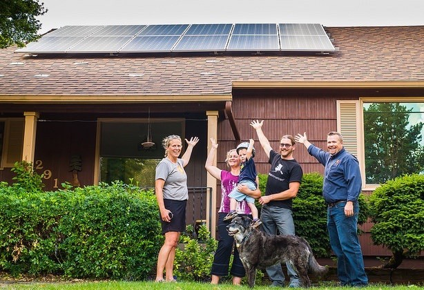 Happy home owners from Seeds for the Sol project show off their new solar panels