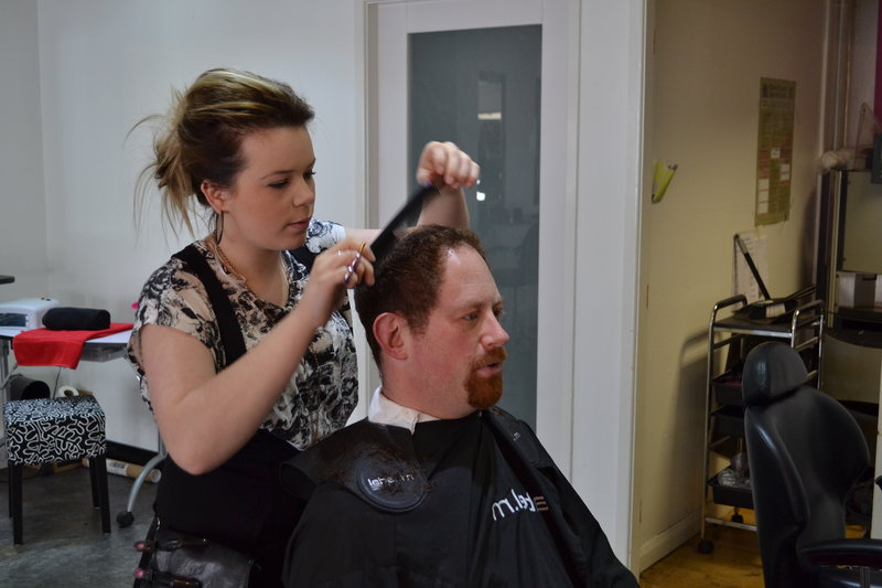 Julian Huppert has his hair cut by hairdressing apprentice Ellena Whitely