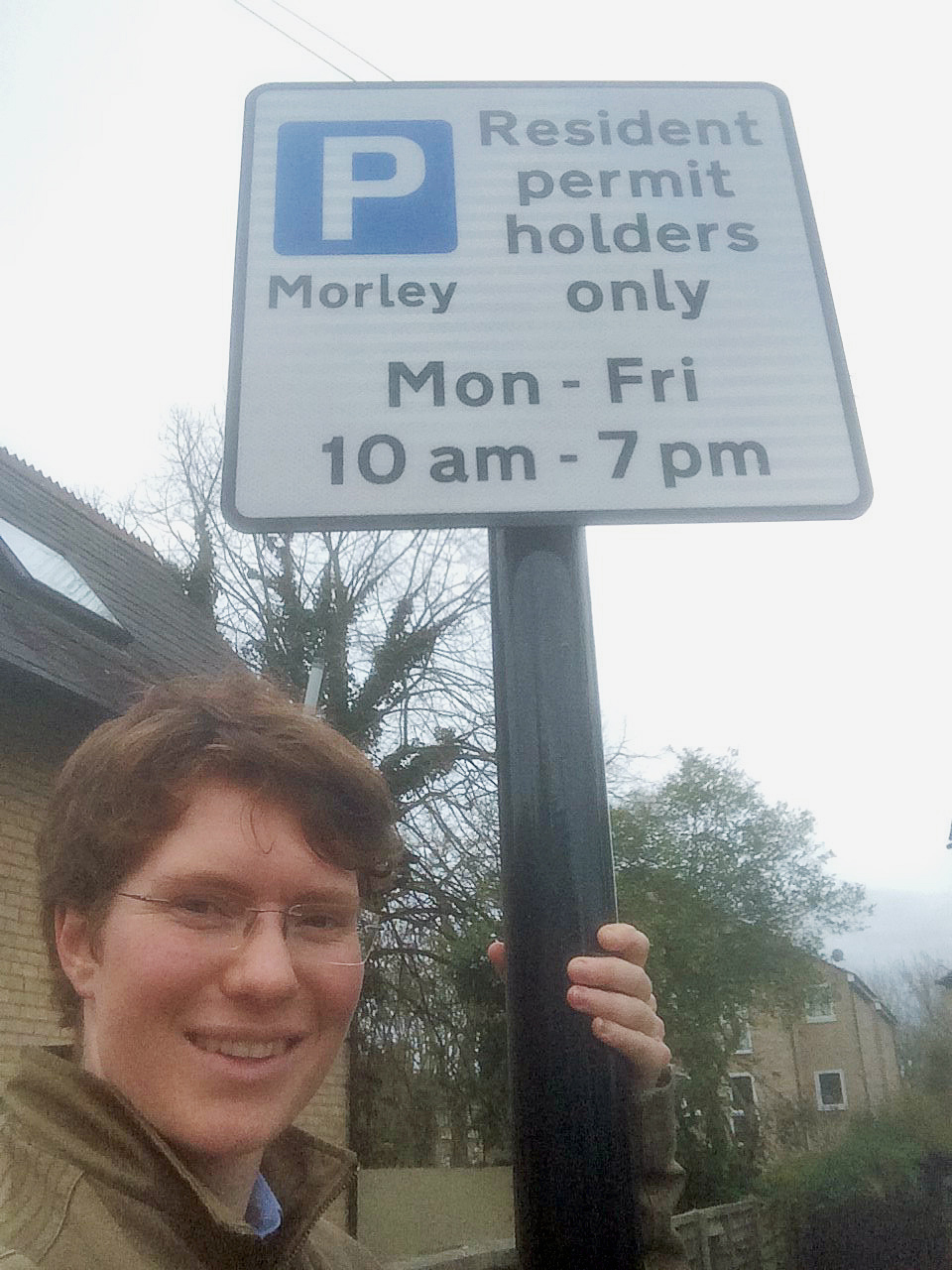 A selfie of a similing person with a signpost, which reads: Residents permit holders only Mon-Fri 10am-7pm, with trees and houses in the background.