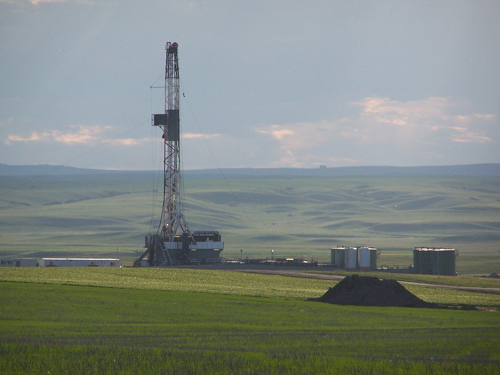 drilling rig on green prairies in Alberta