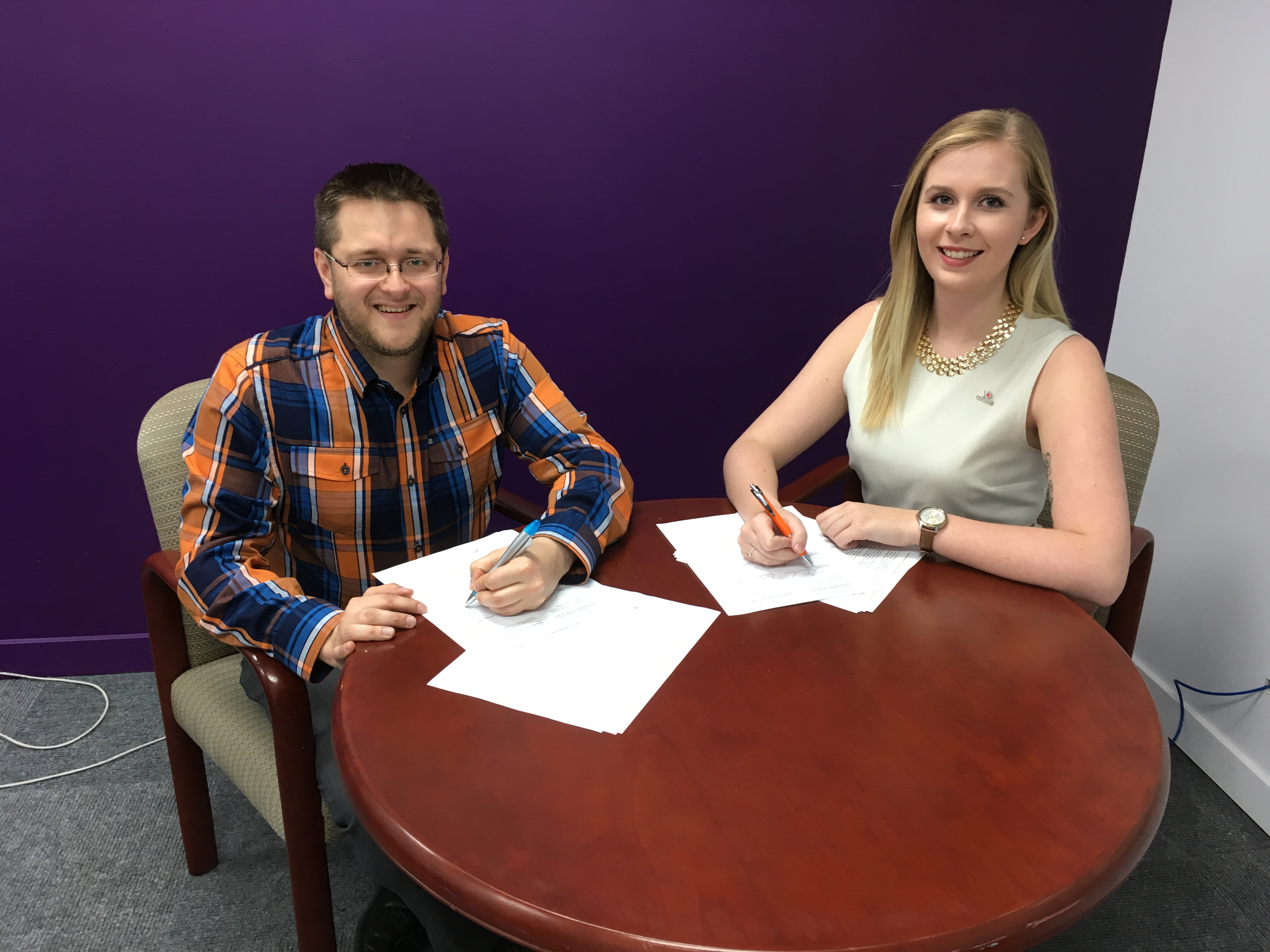 Un représentant de l'UEQ et une représentante de l'ACAE signant le partenariat