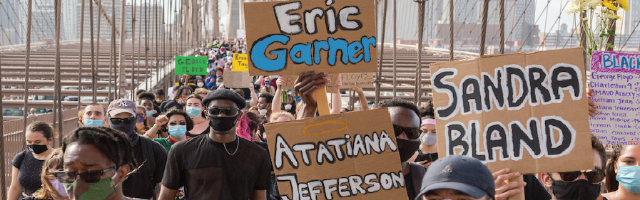 People marching on a bridge holding up Black Lives Matter signs with names of victims