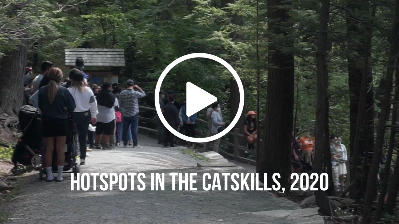 Screen grab of a long line of people at a trailhead with a play button and text that says \